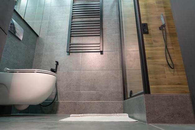 Вид с этажа на аккуратную компактную ванную комнату и туалет