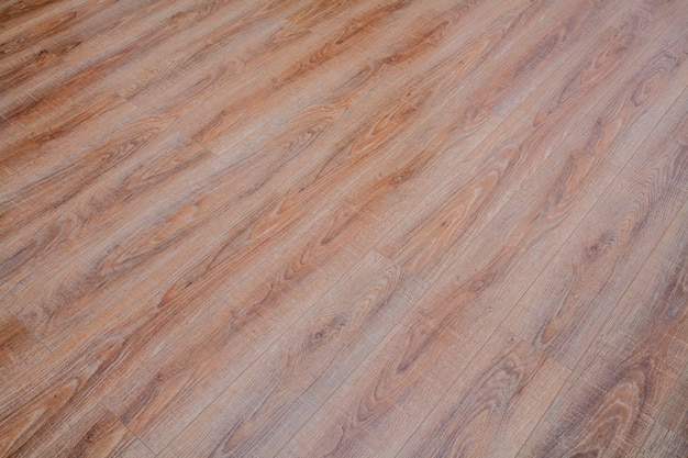 The floor of the light brown laminate diagonally.