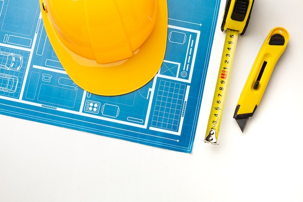 Floor plan, hard hat, tape measure on white