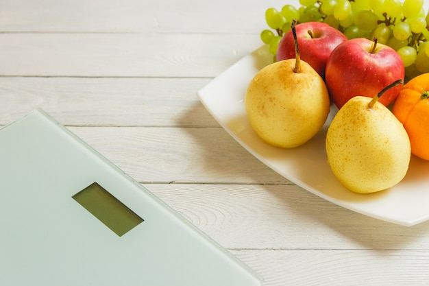 Floor scale and fruits on wooden table