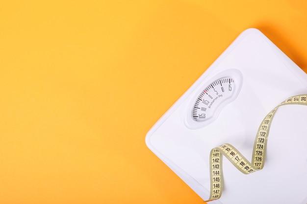 Напольные весы и рулетка на цветном фоне сверху