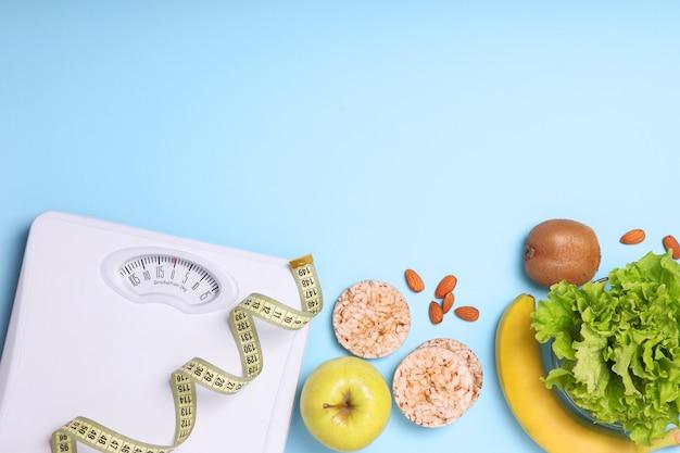 Напольные весы рулетка и здоровые продукты на цветном фоне вид сверху