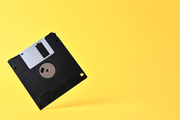 黄色の背景にフロッピーディスク。レトロなコンピュータディスケット