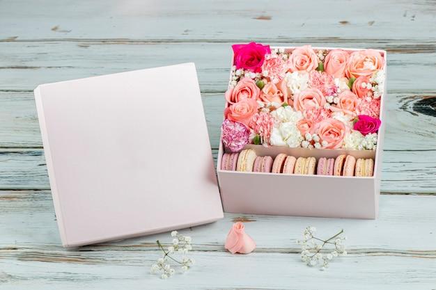 さまざまな色のマカロンとピンクのバラのフラワーアレンジメント