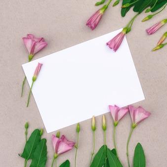 회색 배경에 분홍색 야생화의 꽃꽂이. 디자인을 위한 장소가 있는 인사말 카드.