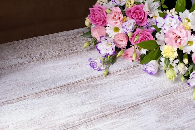 Цветочная композиция из роз, ромашек, лизиантусов, хризантем, фон неоткрытых бутонов
