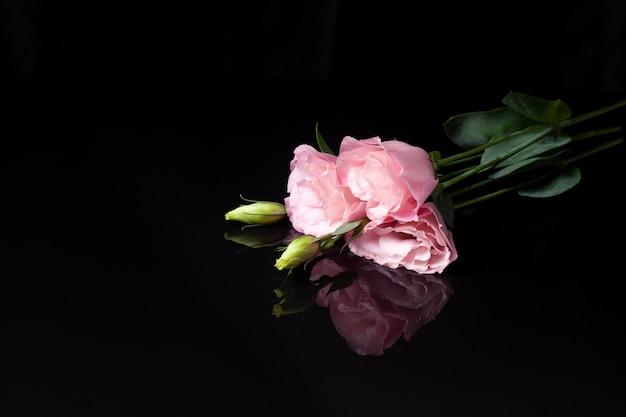 Цветочная композиция из трех розовых цветов лизиантуса или эустомы с нераспустившимся бутоном