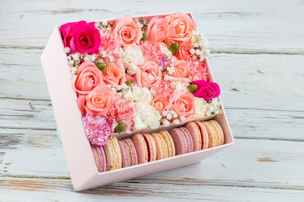 Floral arrangement of pink roses with macarons of different colors