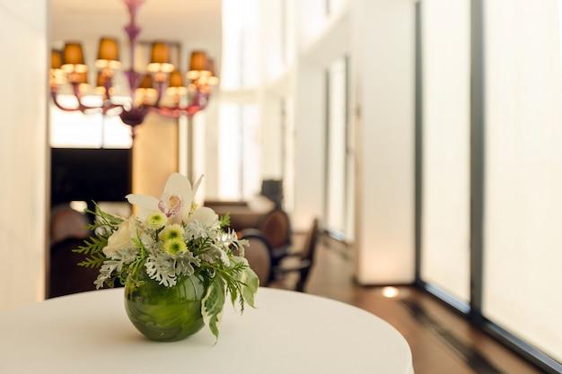 Floral arrangement in round vase on table