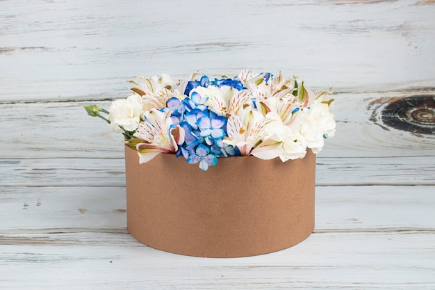Floral arrangement with blue hydrangeas in recyclable cardboard box
