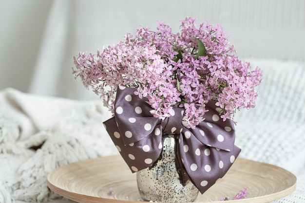 Composizione floreale con fiori lilla freschi e un fiocco come dettaglio decorativo