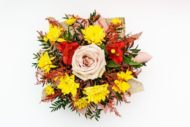 Floral arrangement yellow chrysanthemum and pink rose in flower bouquet on white surface