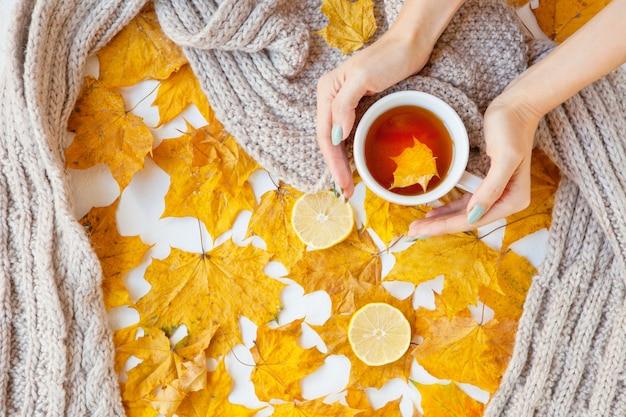 花の秋の背景。黄色い落ち葉のカエデと女性の手にお茶のマグカップ。秋の季節。フラットレイファッションドリンク組成物。カップを保持している女性の手。灰色のスカーフとレモン