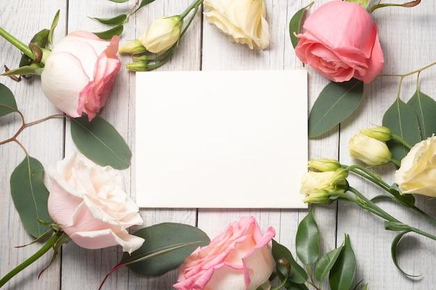 花の背景と空白の白いカード。トルコギキョウ、ユーカリ、ピンクのバラ。休日のコンセプトとコピースペース。高品質の写真