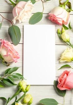 花の背景と空白の白いカード。トルコギキョウ、ユーカリ、ピンクのバラ。