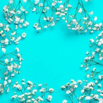 Floral background composition with small white gypsophila flowers on deep blue table