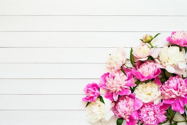 白い木製の背景の誕生日のバレンタインに美しいピンクの白い牡丹と花の背景