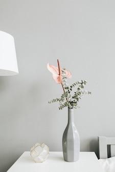 パステルカラーの壁のテーブルの上のボトルのピンクのアンスリウムの花とユーカリの枝の花の花束。最小限のモダンなトレンディなインテリアデザインのコンセプト。