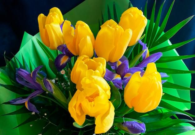 Цветочный букет из желтых тюльпанов и ирисов в красивой зеленой оберточной бумаге. крупный план. продажа цветочных букетов.