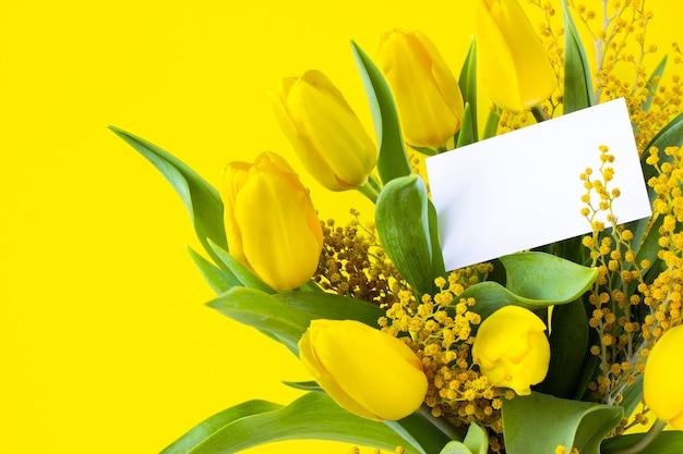 空白の白いグリーティングカードのモックアップと花の花束。黄色いチューリップとミモザ、緑の葉。明るい背景