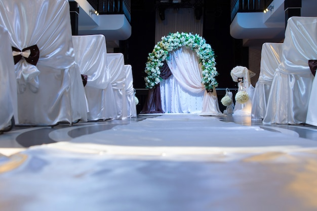 Floral bridal bower above a small altar with decorative white chairs tied in linen and bows viewed low angle along the aisle at a wedding venue