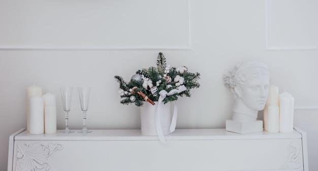 전나무 가지, 면, 계피 스틱, 크리스마스 공이 있는 흰색 모자 상자에 꽃 크리스마스 구성이 있습니다. 세련된 새해와 크리스마스의 개념