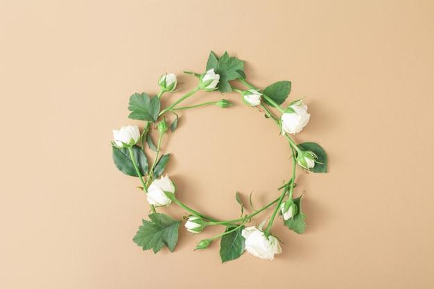 Цветочный круг на бежевом светло-коричневом фоне. круглая рамка из белых роз. минималистичная цветочная художественная композиция