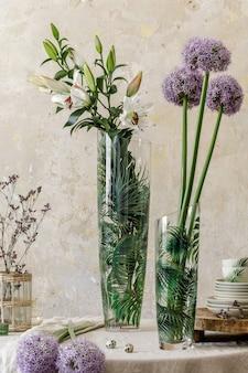 나무 가족 테이블, 꽃병에 있는 아름다운 꽃, 접시, 컵, 쟁반, 우아한 장식이 있는 주방 인테리어의 꽃 구성. 현대적인 가정 장식의 식당. 주형.