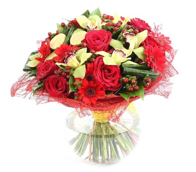 유리, 투명 꽃병에 꽃 조성 : 빨간 장미, 난초, 빨간 거베라 데이지. 흰색 배경에 고립.
