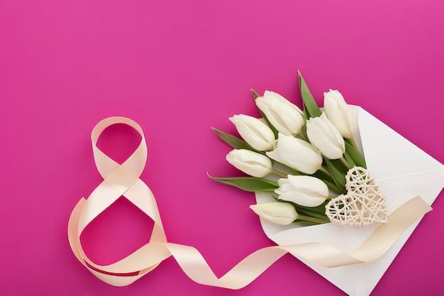 Цветочная композиция в белом конверте, белые тюльпаны и сердце, и атласная цифра восемь на розовом.