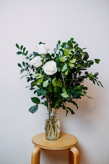 Floral composition in interior. bunch with white roses and green leaves. flowers in flower bowl with water on the wooden table.