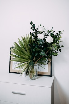 Floral composition in interior. bunch with white roses and green palm leaves. flowers in flower bowl with water.