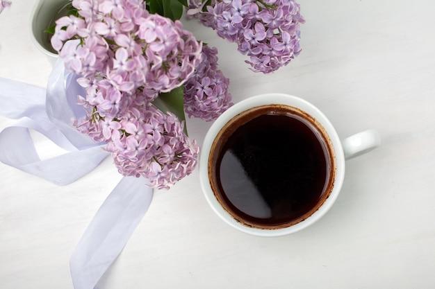Цветочная композиция из красивой фиолетовой сирени на белом деревянном фоне с чашкой кофе, стилизованное изображение, плоская планировка, вид сверху