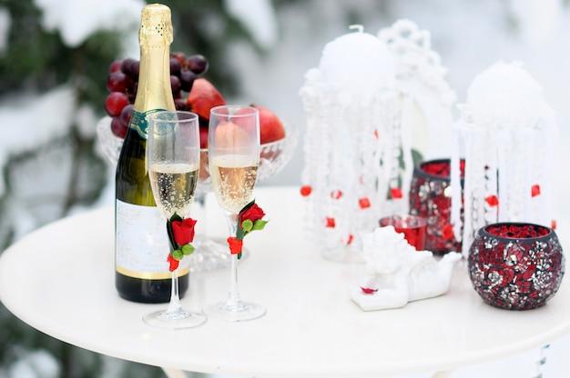 Цветочная композиция из красных роз, на снежном столе в зимнем лесу, концепция декора зимней свадьбы