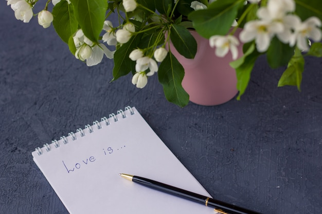 Floral composition on a spring day. blossoming branches of apple tree in a pink mini vase on a grey background. notebook with space for text. concept of writing a romantic letter.