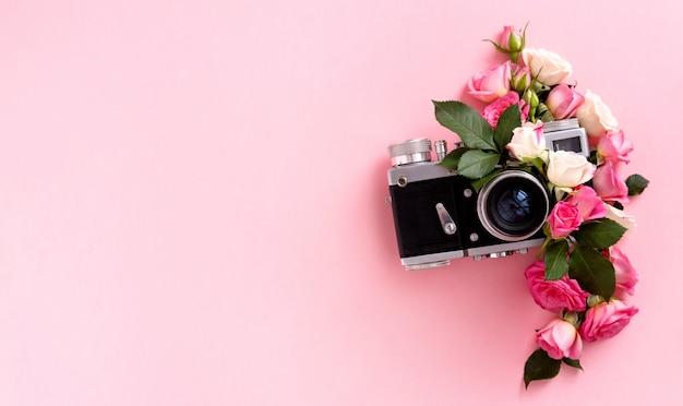 Цветочная композиция с венком из розовых роз и камеры на розовом фоне. день святого валентина фон. плоская планировка, вид сверху.