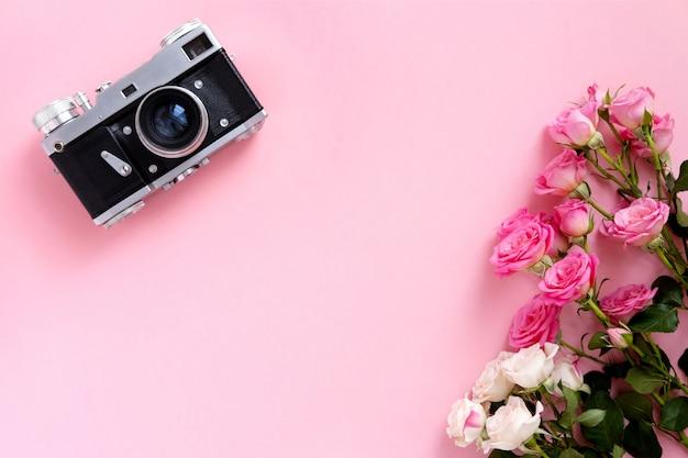 Цветочная композиция с венком из розовых роз и ретро камеры на розовом фоне. день святого валентина фон. плоская планировка, вид сверху. Premium Фотографии
