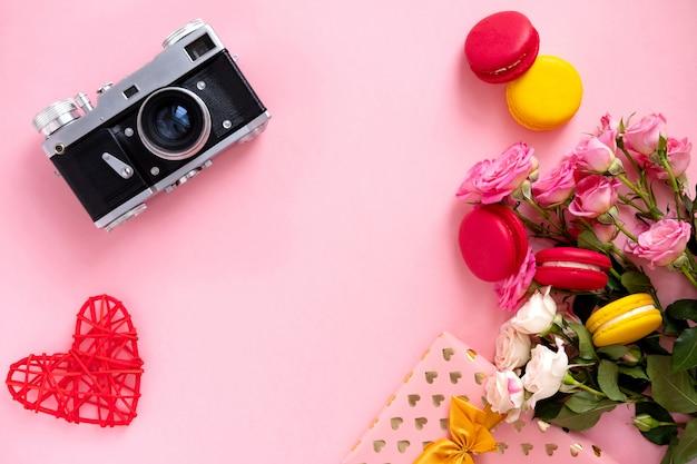 ピンクのバラとピンクの背景にレトロなカメラの花輪を持つ花の組成。バレンタインデーの背景。フラット横たわっていた、トップビュー。