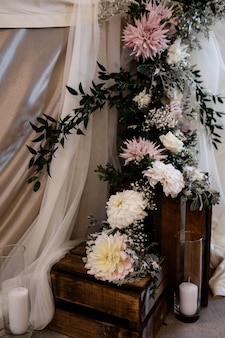 Floral composition with candles on the wooden boxes for the wedding ceremony