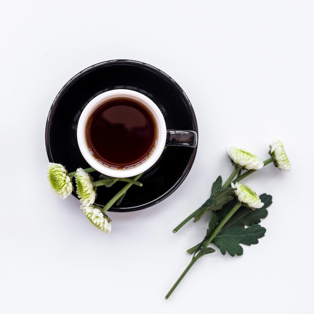 Floral composition with cup of  black coffee and flowers