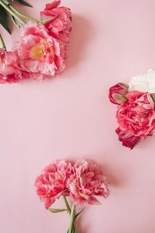 Цветочная композиция с круглой рамкой из розовых и белых цветов пиона на розовом. плоская планировка, вид сверху