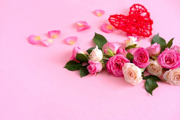 Floral composition with a wreath of pink roses on pink background.