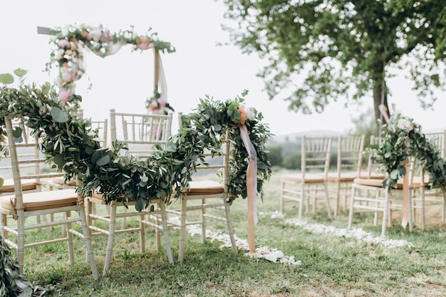 Floral compositions made of greenery at the outdoors wedding ceremony