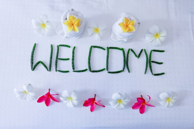 Floral decor, towel floral and word welcome on bed in hotel room