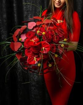 アンスリウムの花束を保持している花の装飾の女性