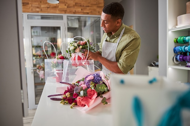 Floral designer at a white table with a flower pot in his hands carefully lowering it in a transparent bag
