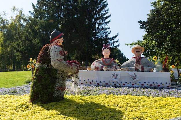 公園の屋外でのクリエイティブアートの展示会で、生花で作られた服を着てテーブルに座っている男性と女性にお茶を提供する使用人の花の展示