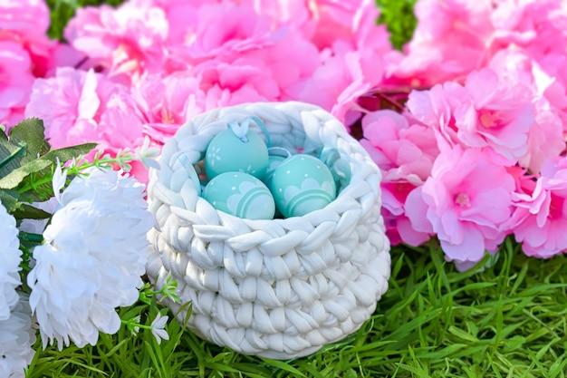 花のイースター。緑の草のかぎ針編みのバスケットに塗られた卵。