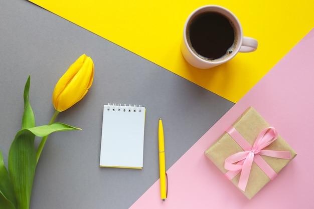 花のお祝いのモックアップ黄色のチューリップの花のギフトボックスのコーヒーと幾何学的な黄色の灰色とピンクの背景に開いたメモ帳