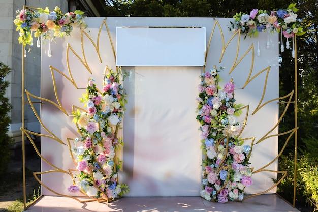 おめでとうテキストのための空白の看板と花のお祝いの結婚式のアーチ。特別な日のために